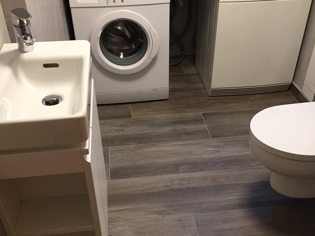 WC und Wirtschaftsraum mit Holzfliesen.