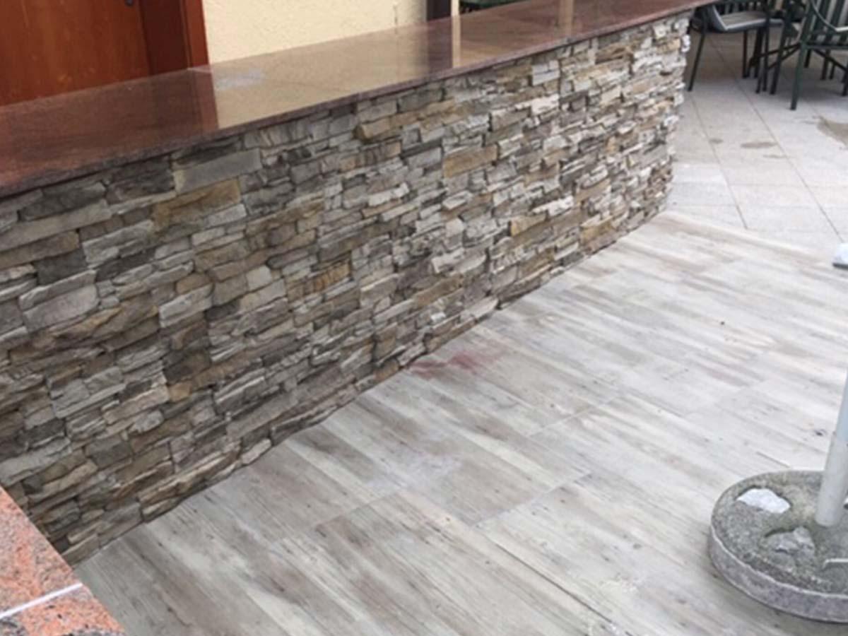 Holzfliesen und rustikale Steinmauer